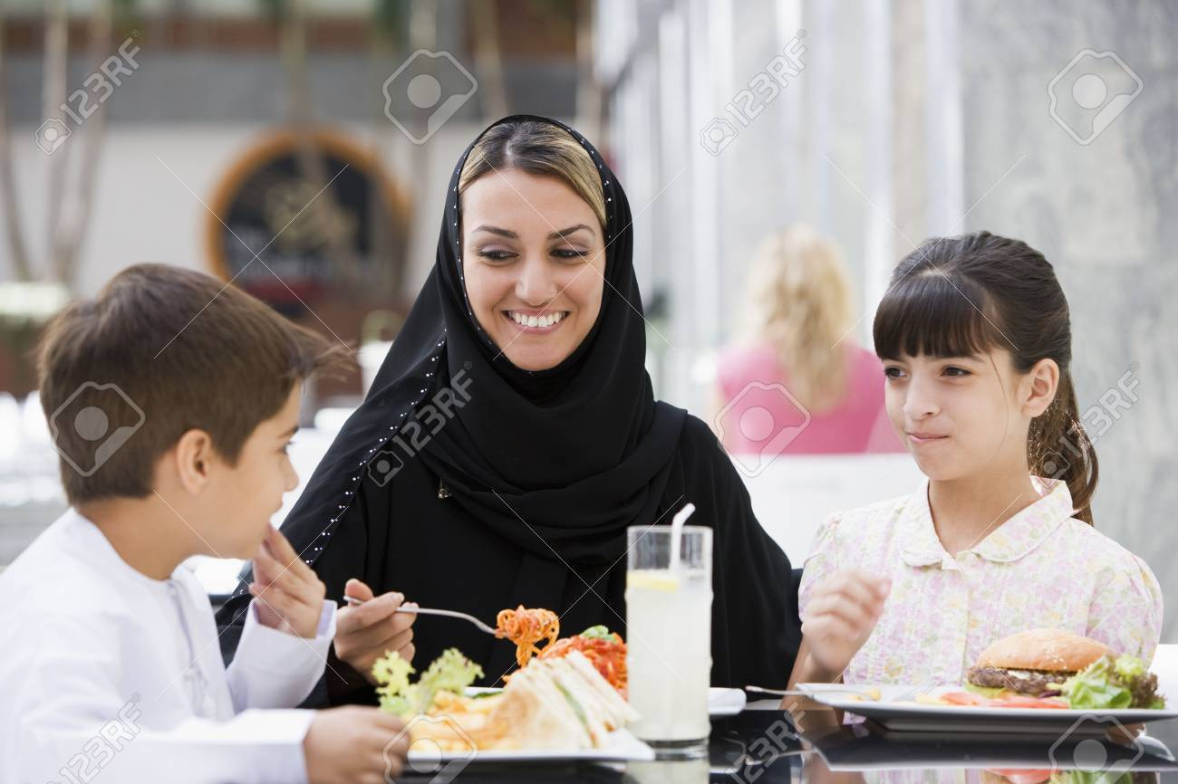 Woman and two young children at restaurant eating and smiling (selective focus) Stock Photo - 3186765