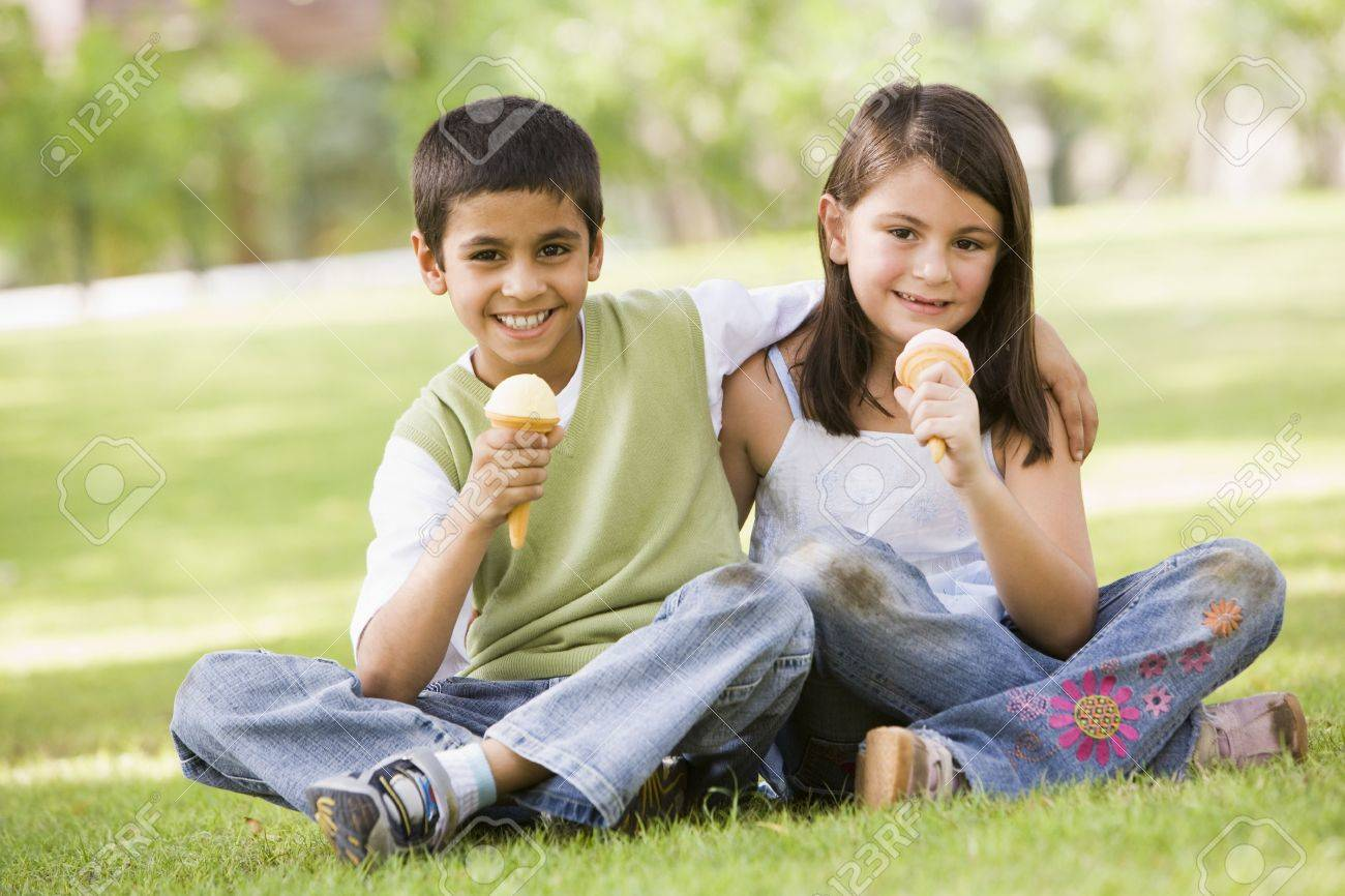 Two young children outdoors in park with ice cream smiling (selective focus) Stock Photo - 3186641