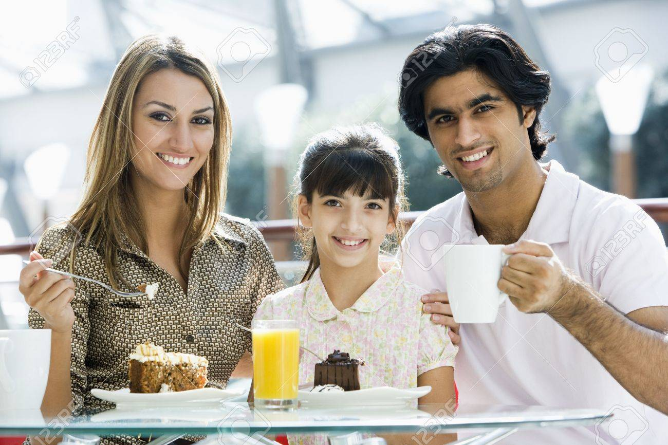 Family at restaurant eating dessert and smiling (selective focus) Stock Photo - 3186274