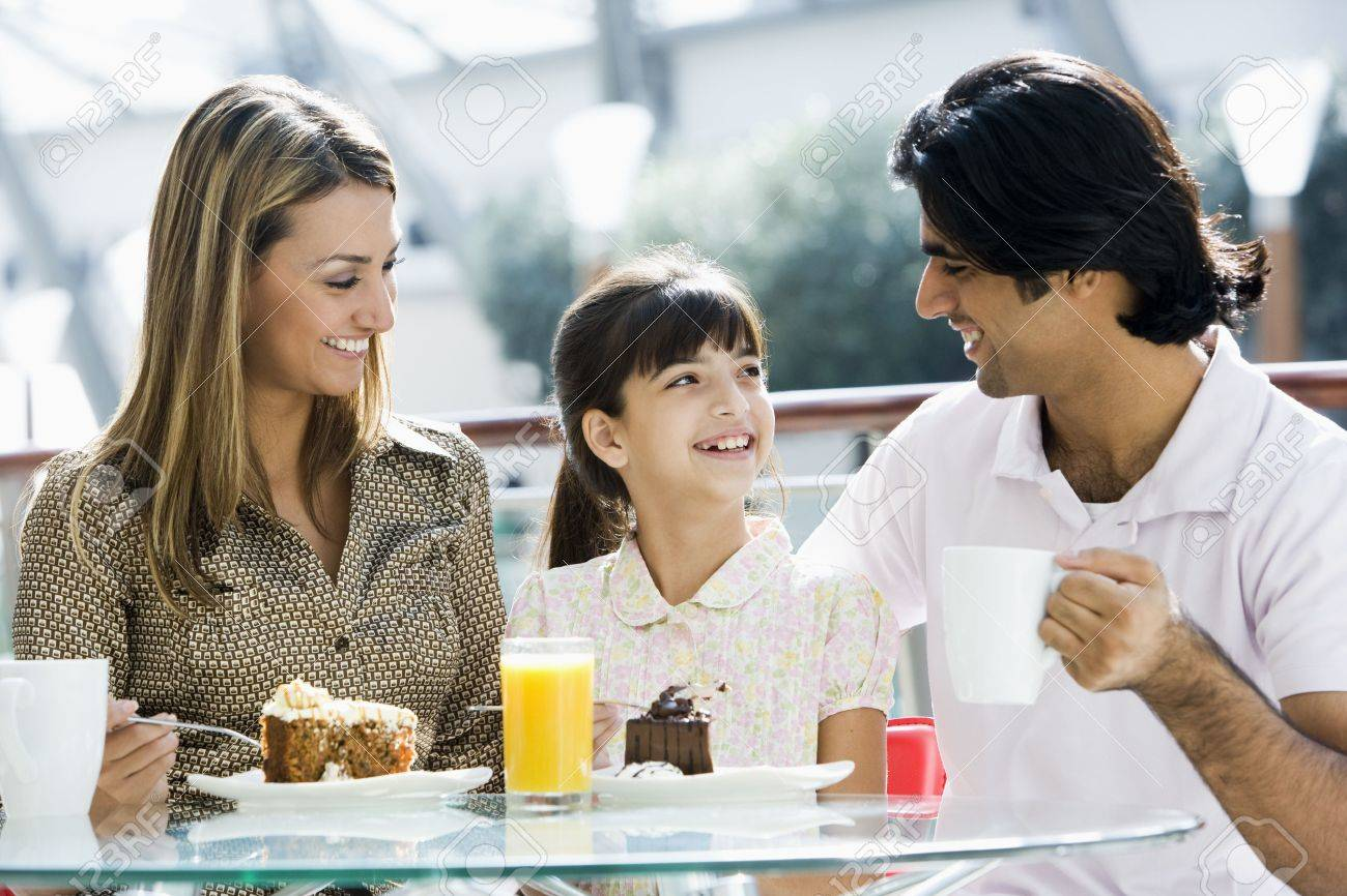 Family at restaurant eating dessert and smiling (selective focus) Stock Photo - 3186313