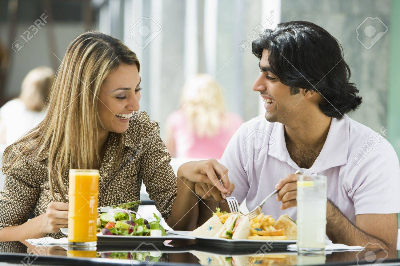 Couple at restaurant eating and smiling (selective focus) Stock Photo - 3186563