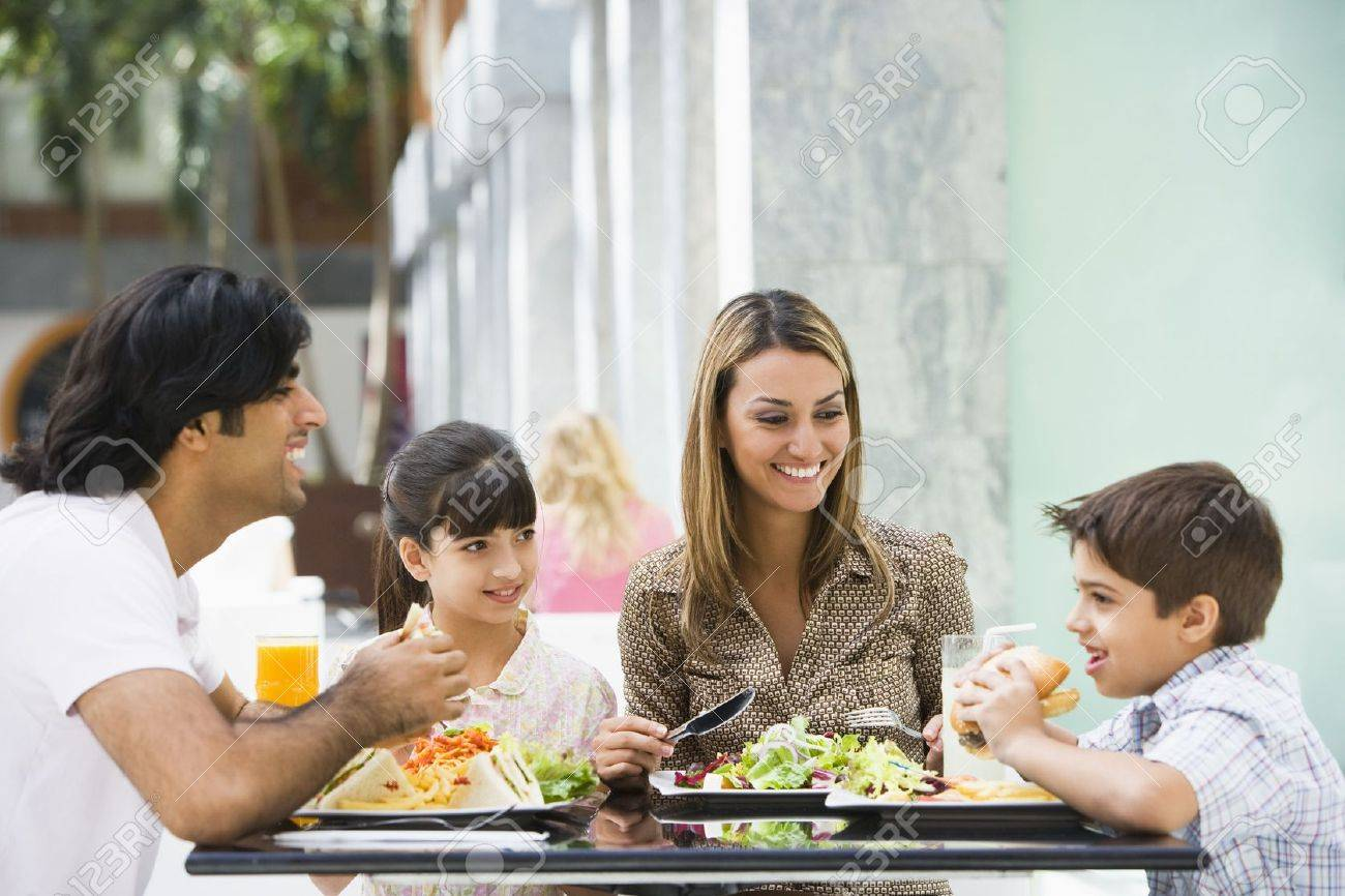 Family at restaurant eating and smiling (selective focus) Stock Photo - 3186662