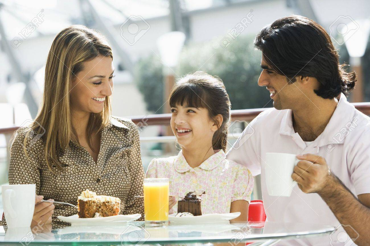 Family at restaurant eating dessert and smiling (selective focus) Stock Photo - 3186512