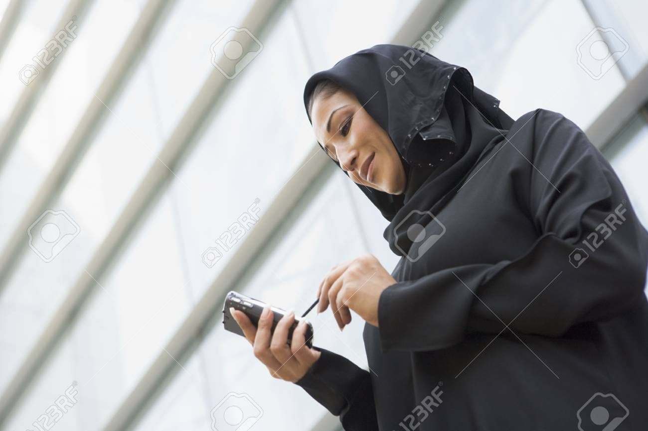 Businesswoman outdoors by building using personal digital assistant and smiling (selective focus) Stock Photo - 3170892