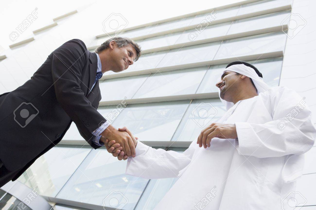 Two businessmen outdoors by building shaking hands and smiling (high key/selective focus) Stock Photo - 3170900