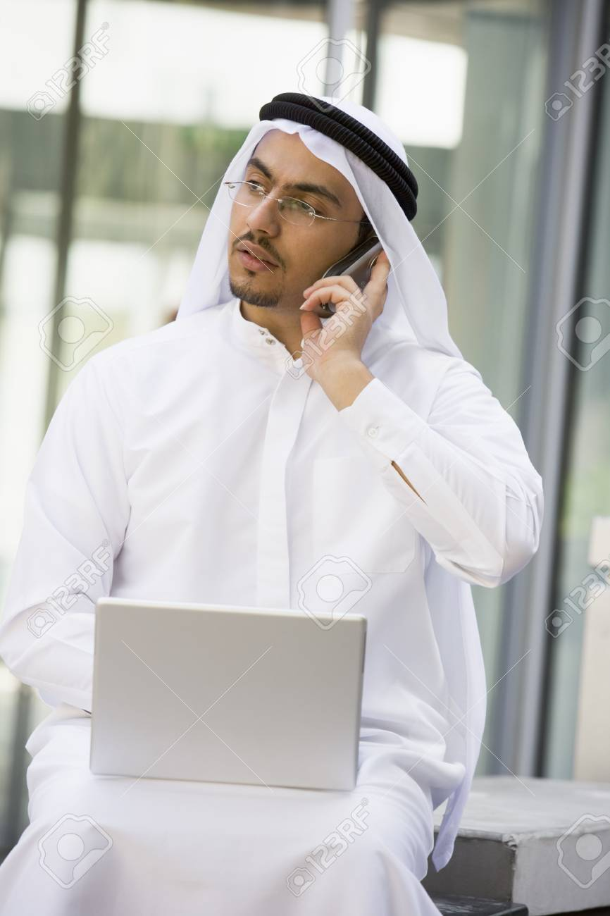 Businessman outdoors with laptop using cellular phone by building (selective focus) Stock Photo - 3170883