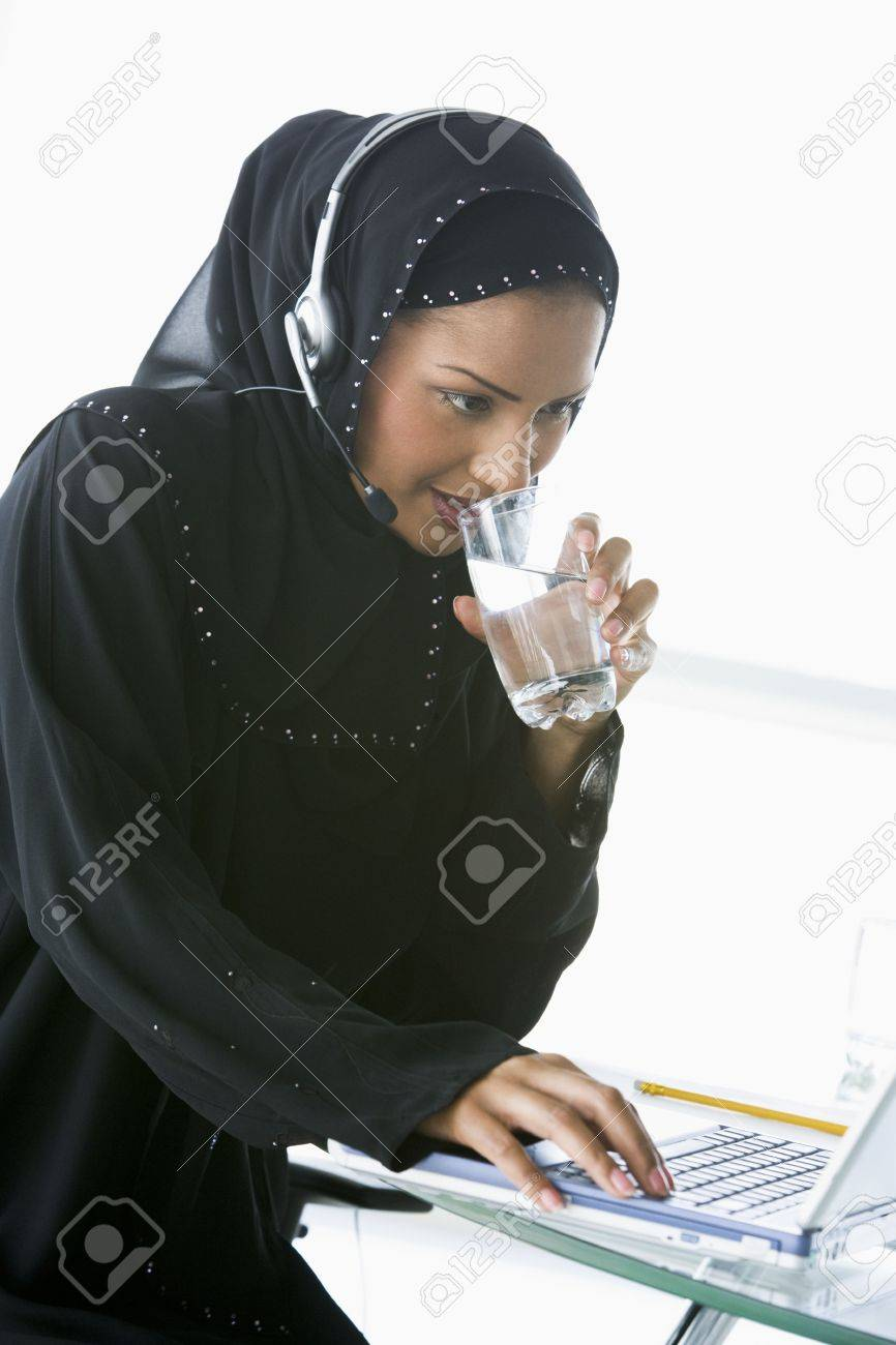 Woman wearing headset with laptop drinking water and smiling (high key/selective focus) Stock Photo - 3171337