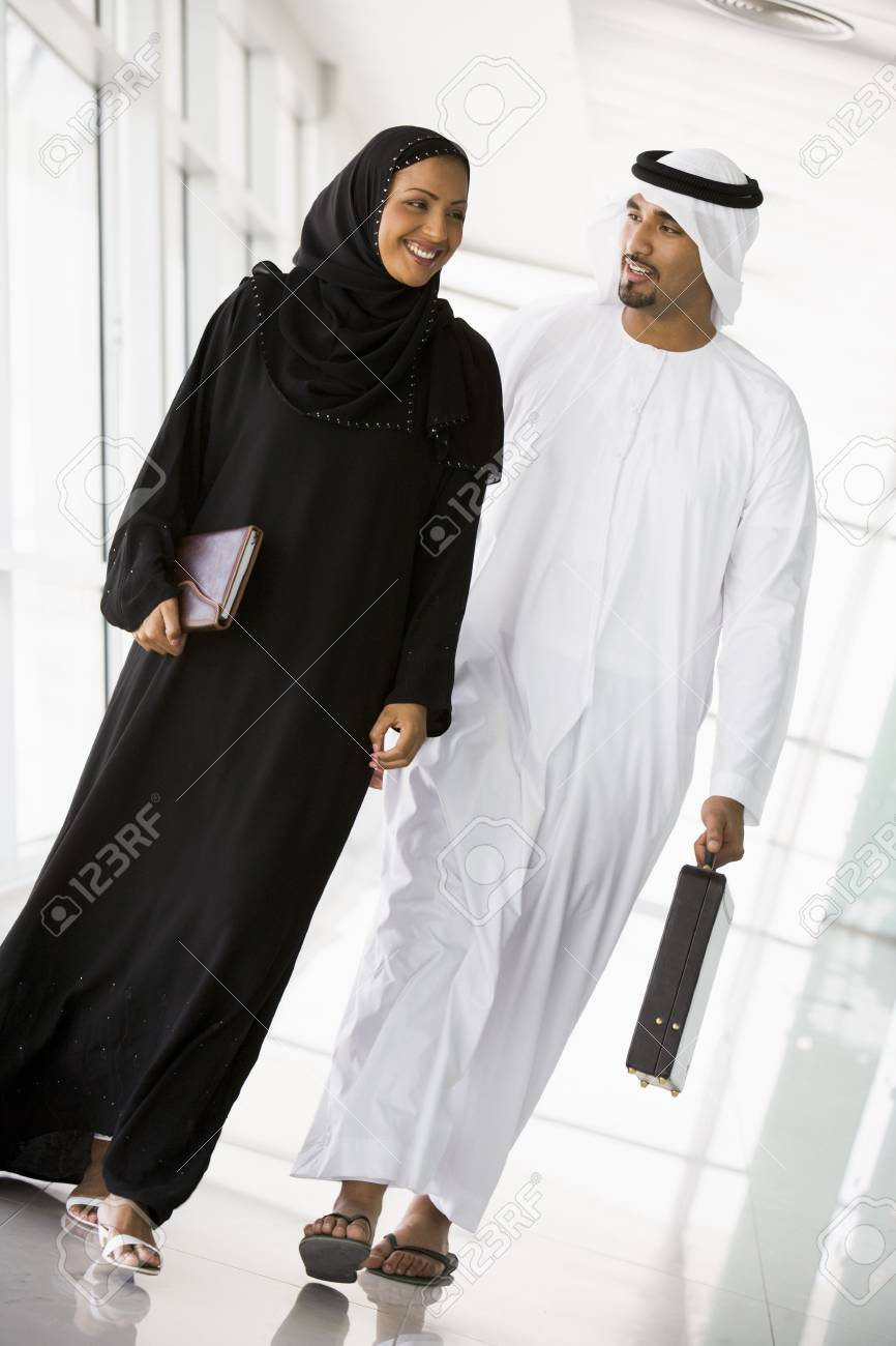 Two businesspeople walking in a corridor and smiling (high key/selective focus) Stock Photo - 3171211