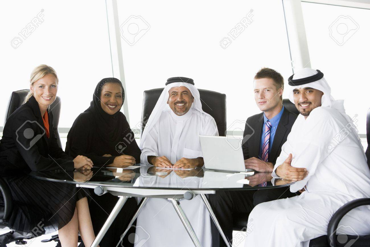Five businesspeople in office with laptop smiling (high key/selective focus) Stock Photo - 3171738