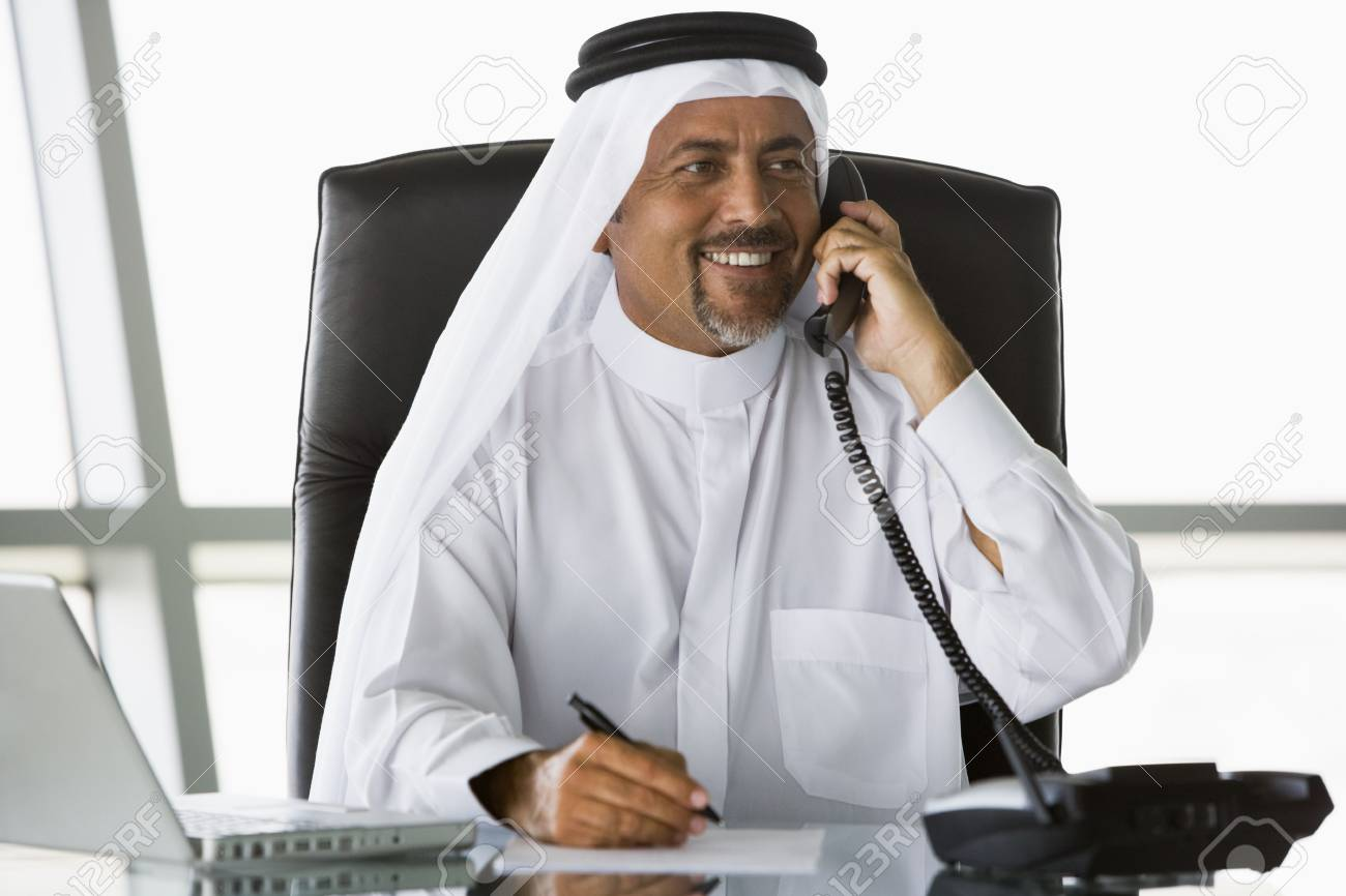 Businessman in office on telephone by laptop smiling (high key/selective focus) Stock Photo - 3171723
