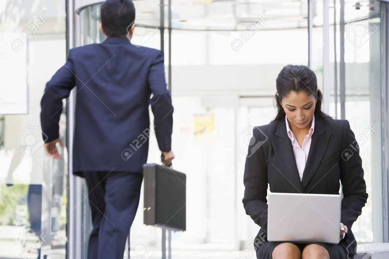 Businesswoman outdoors in front of building using laptop with businessman in background (high key/blur) Stock Photo - 3171234
