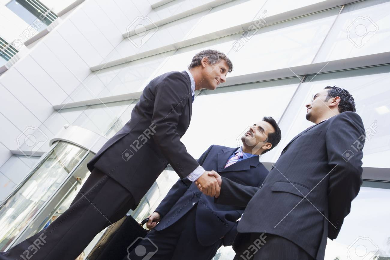 Three businessmen outdoors by building shaking hands and smiling (high key/selective focus) Stock Photo - 3171130