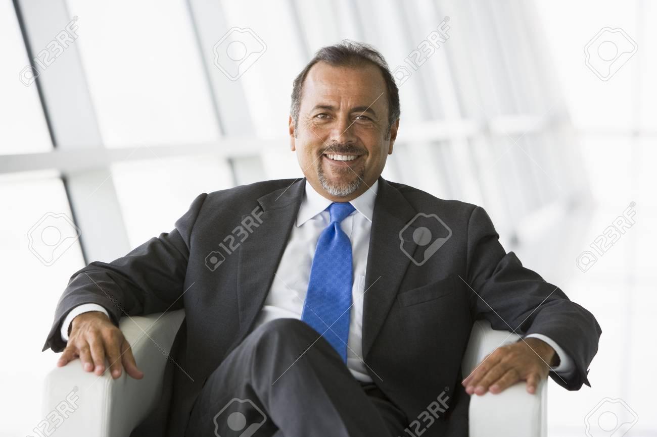 Businessman sitting indoors smiling (high key/selective focus) Stock Photo - 3171737