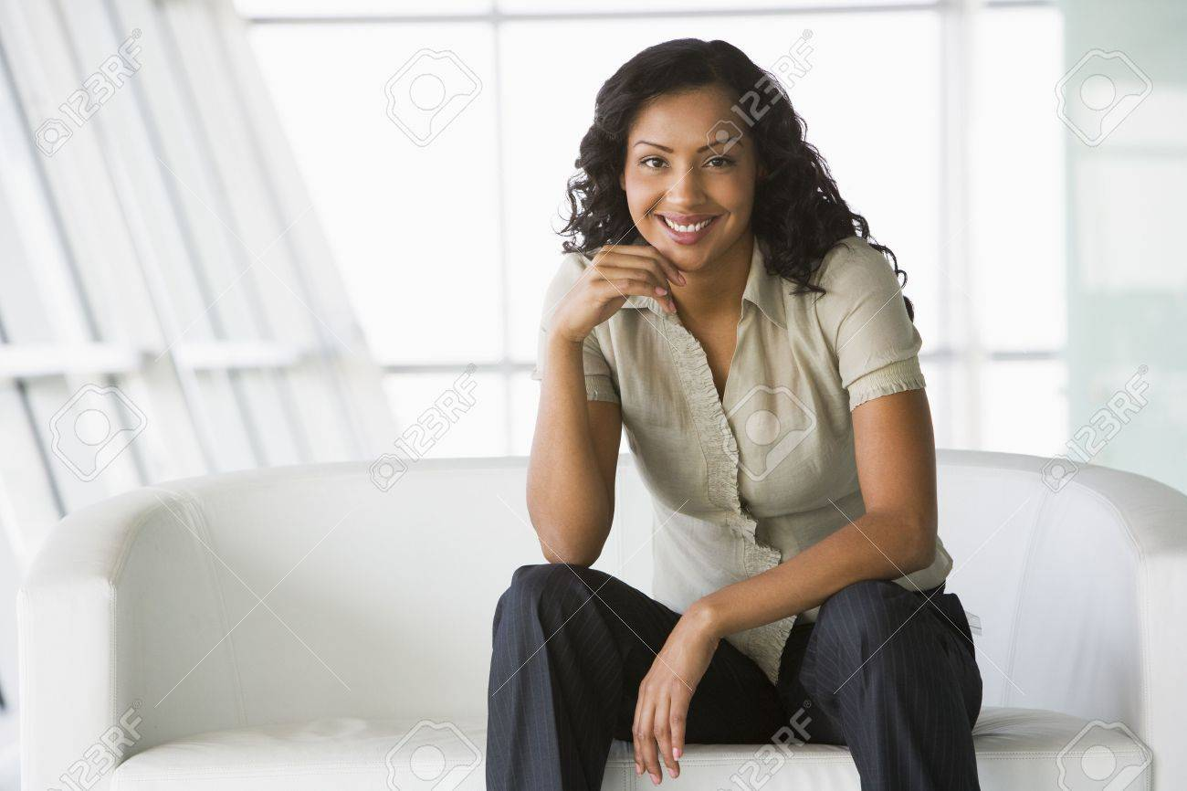 Businesswoman sitting indoors smiling (high key/selective focus) Stock Photo - 3171240