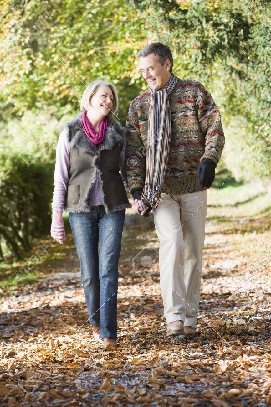 Couple outdoors walking on path in park holding hands and smiling (selective focus) Stock Photo - 3207898