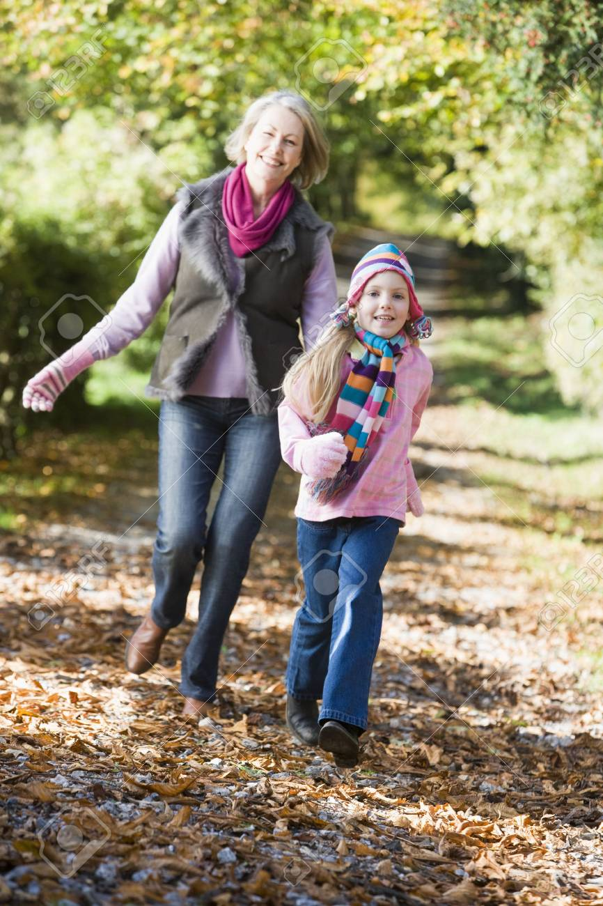 Grandmother and granddaughter running outdoors in park and smiling Stock Photo - 3217910