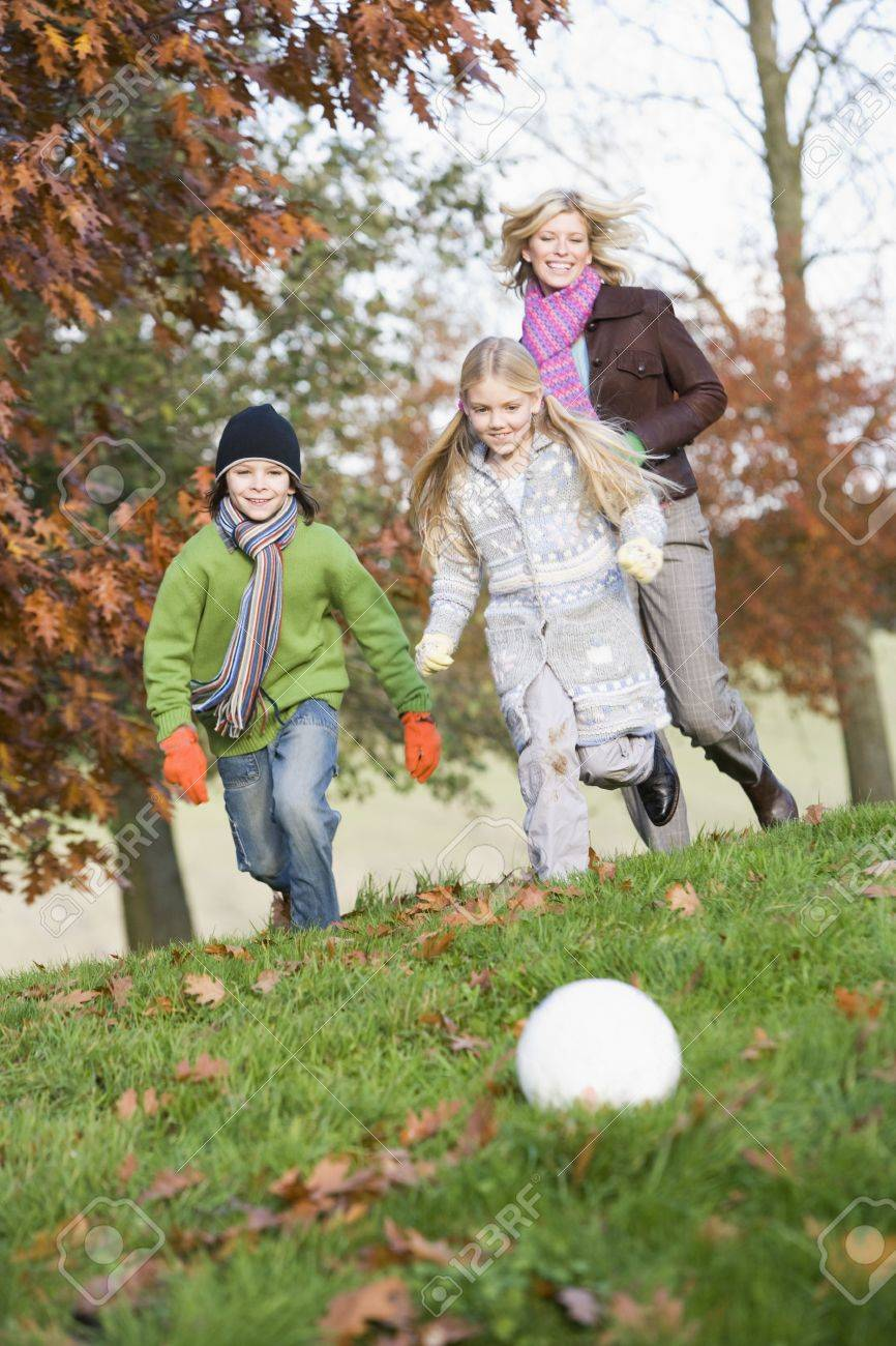 Mother outdoors in park with two young children playing soccer and smiling (selective focus) Stock Photo - 3226269