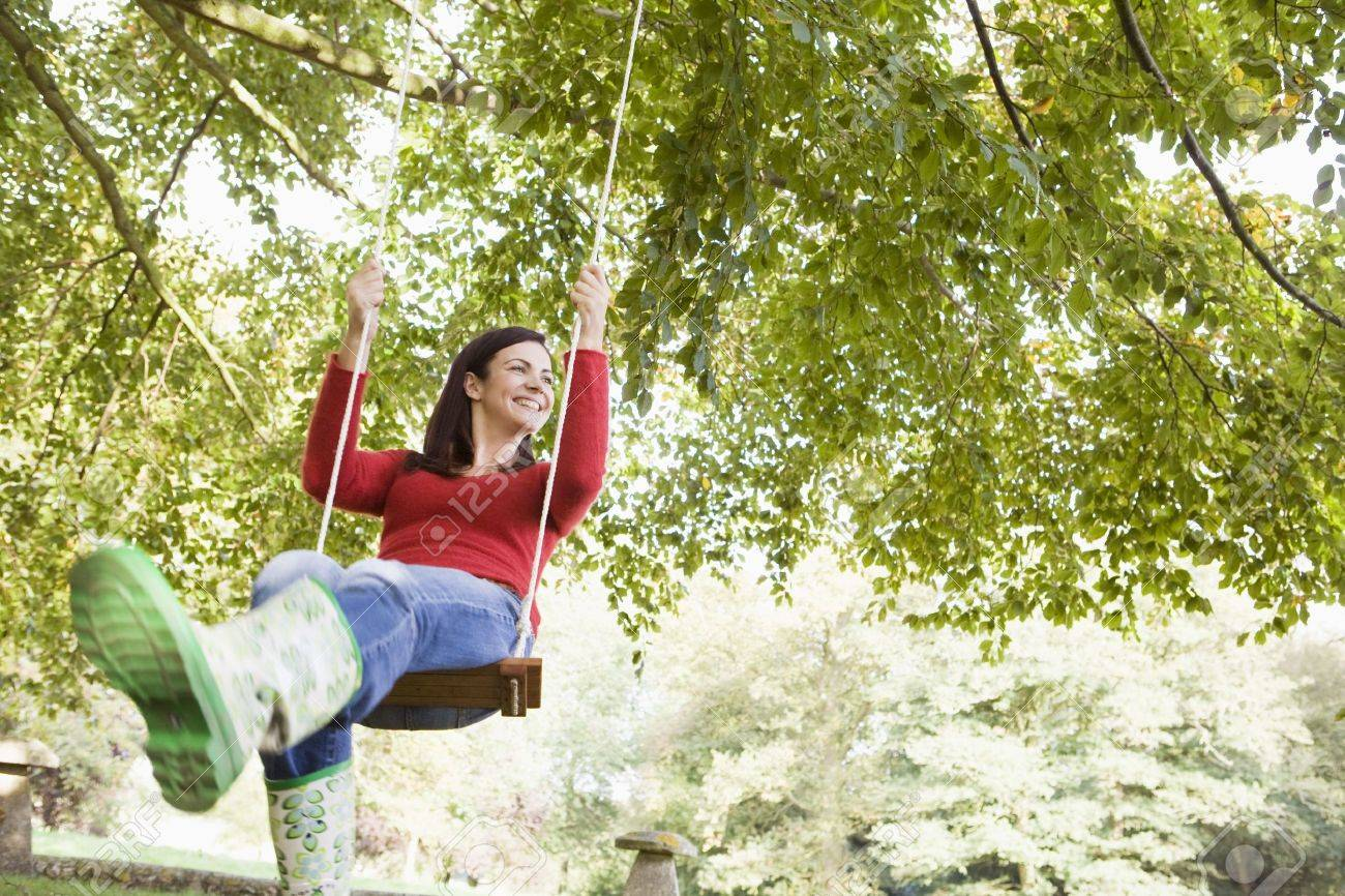 Woman outdoors swinging on tree swing and smiling (selective focus) Stock Photo - 3207855