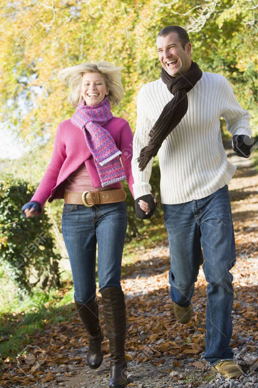 Couple running outdoors on path in park smiling (selective focus) Stock Photo - 3207932