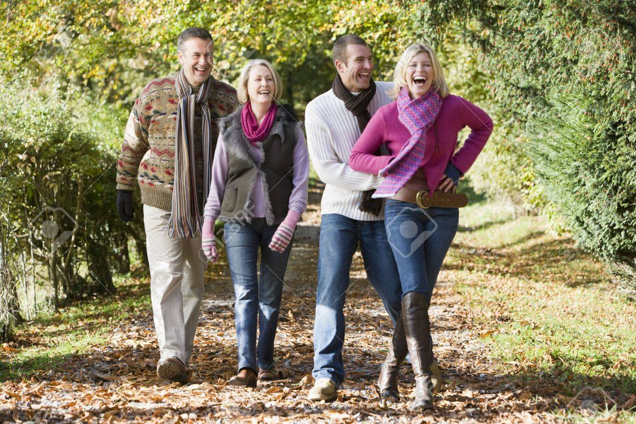 Two couples walking on path outdoors smiling (selective focus) Stock Photo - 3207751