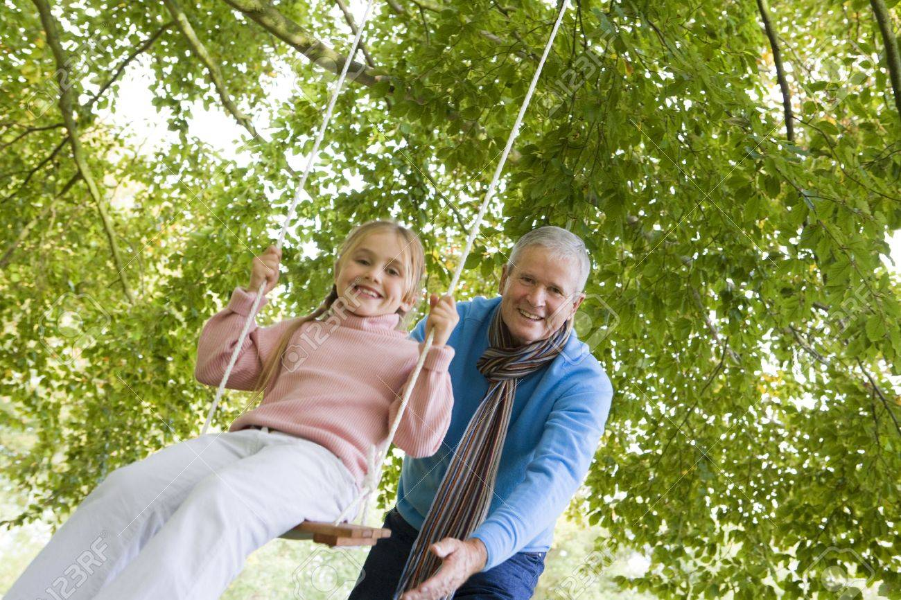 Grandfather outdoors pushing granddaughter on swing and smiling (selective focus) Stock Photo - 3207784