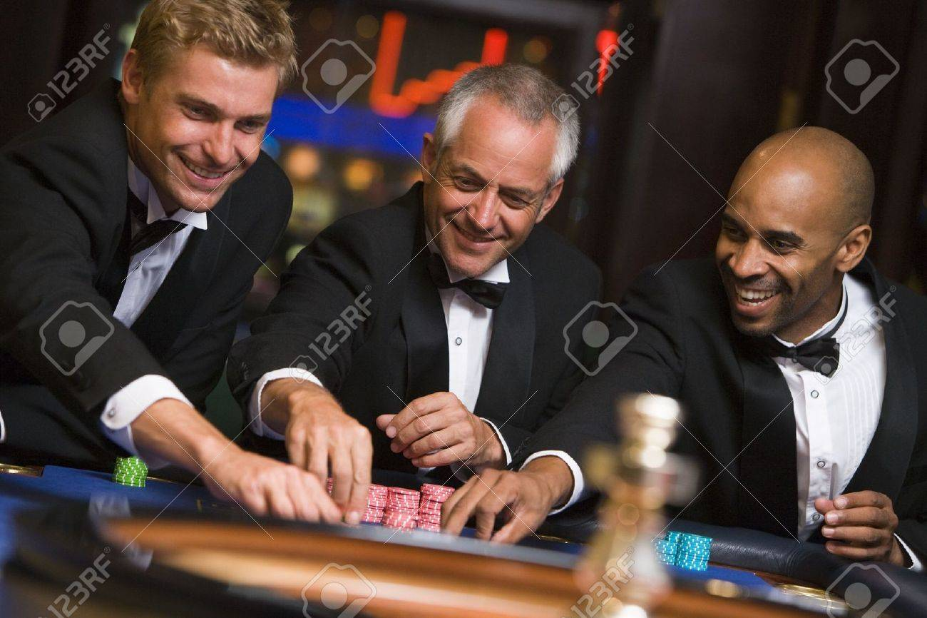 Three men in casino playing roulette smiling (selective focus) Stock Photo - 3194490