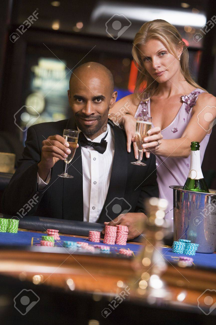 Couple in casino at roulette table holding champagne and smiling (selective focus) Stock Photo - 3194464