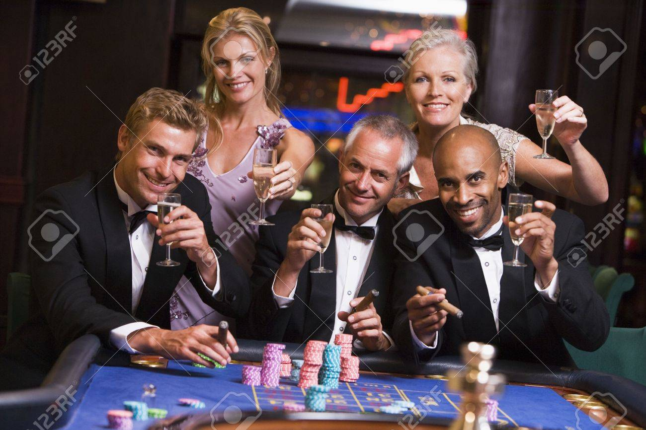 Five people in casino playing roulette and smiling (selective focus) Stock Photo - 3194293