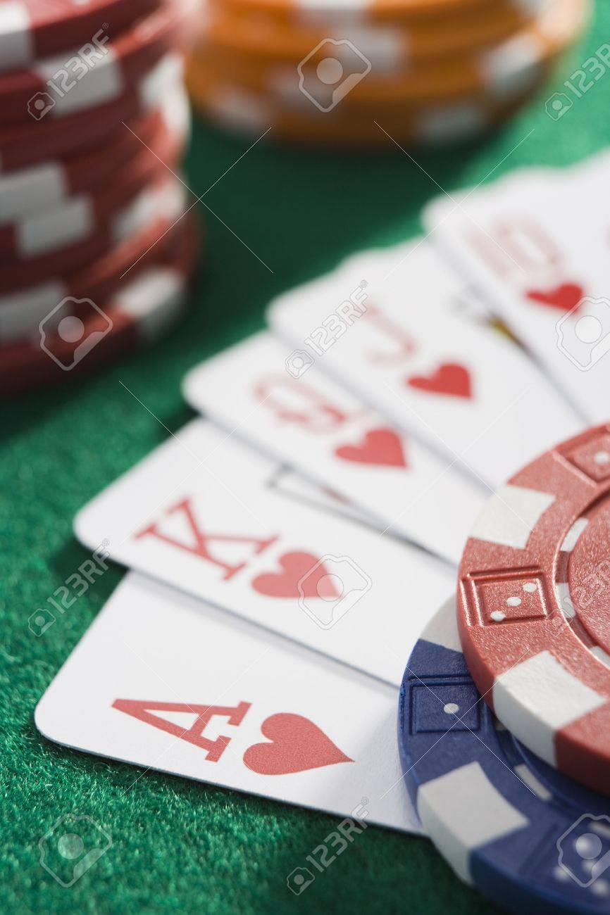 Playing cards making royal flush in hearts by poker chips (close up/selective focus) Stock Photo - 3194529