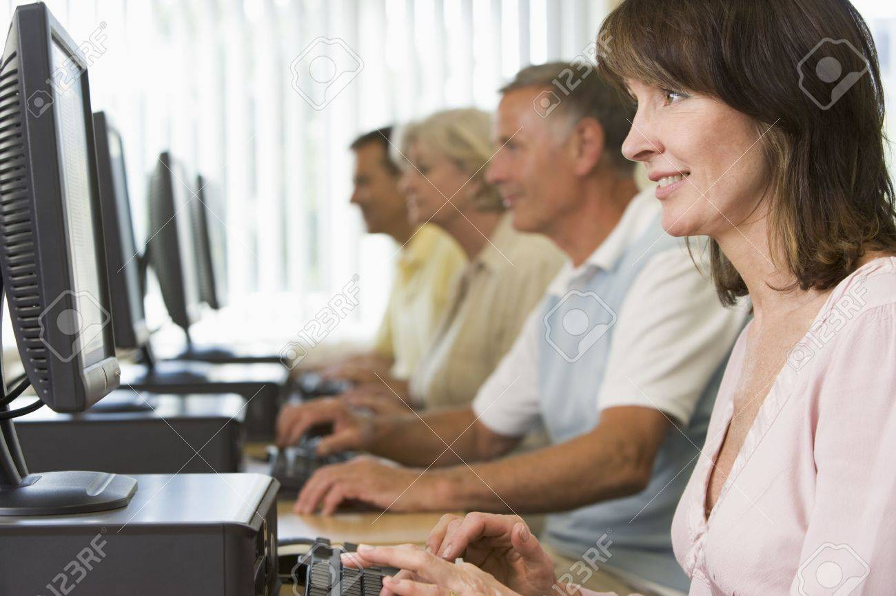 Four people sitting at computer terminals (depth of field/high key) Stock Photo - 3174197