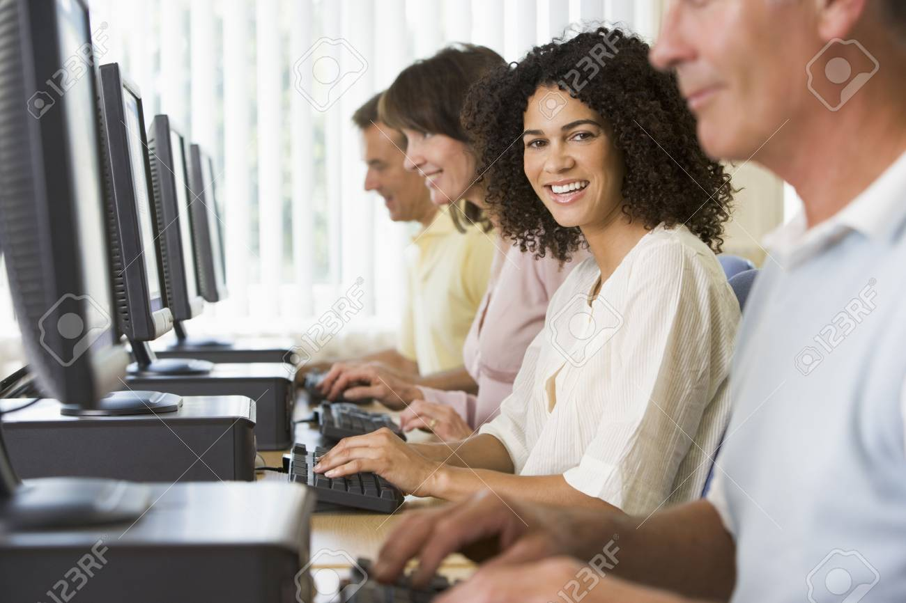 Four people sitting at computer terminals (selective focus/high key) Stock Photo - 3173648