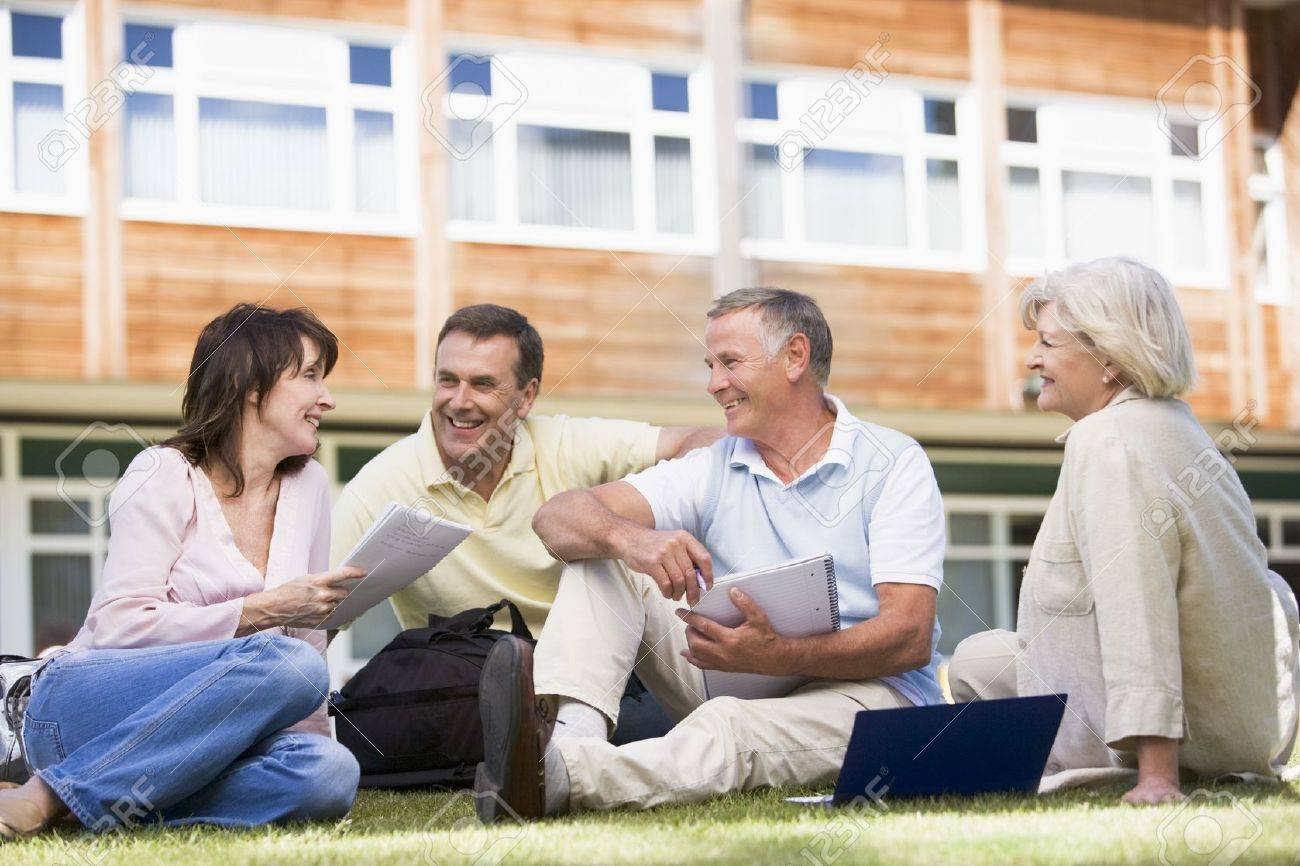 Adult students on lawn of school studying and talking Stock Photo - 3174639
