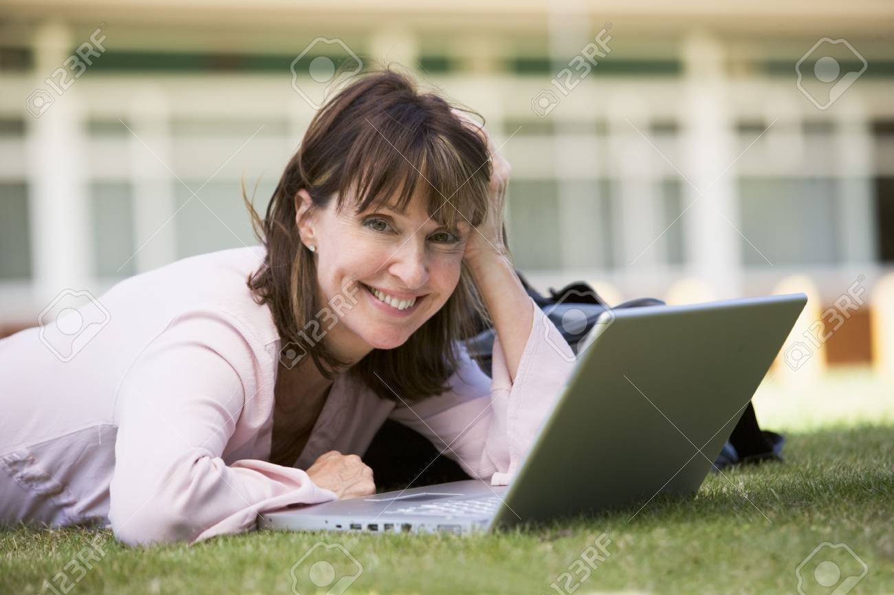 Woman lying on lawn of school with laptop Stock Photo - 3173586