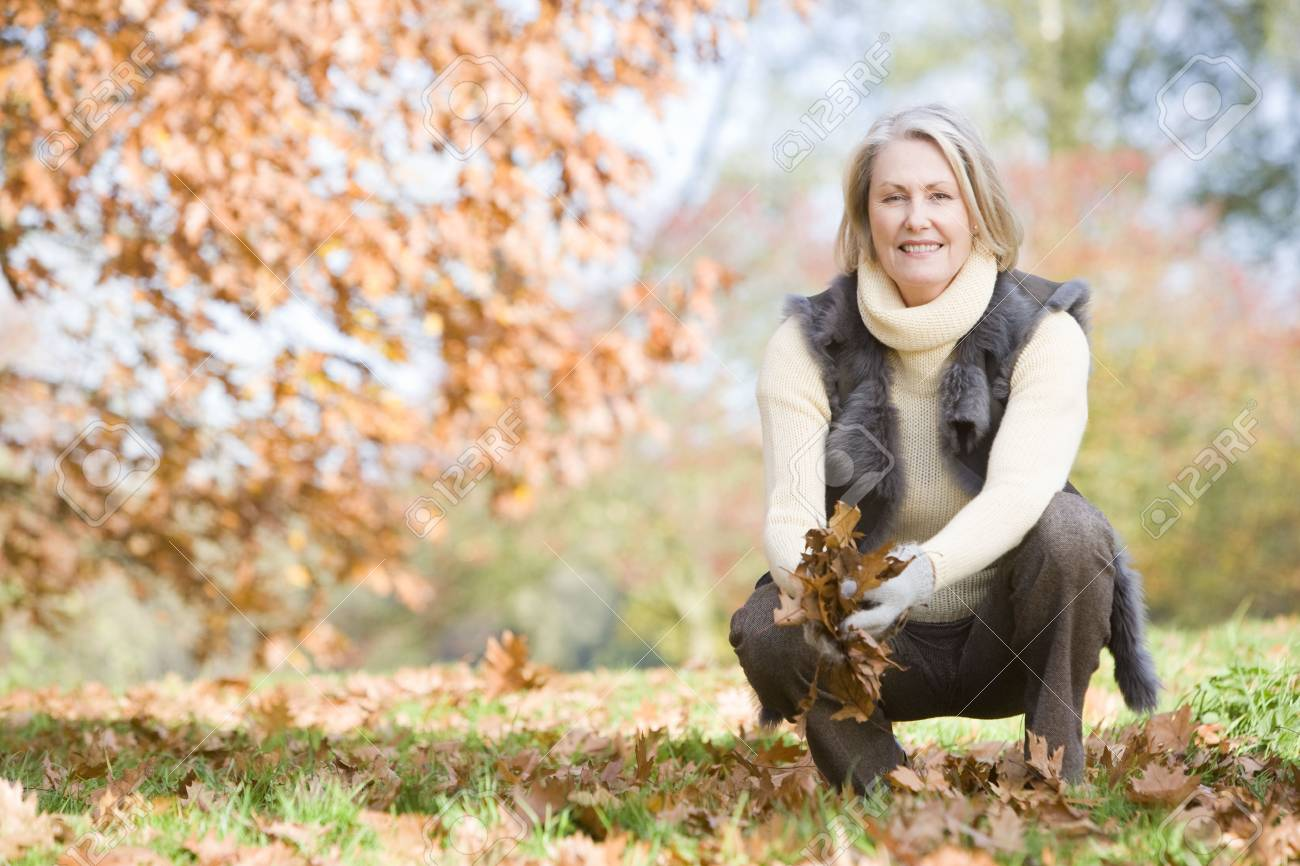 Woman outdoors holding leaves and smiling (selective focus) Stock Photo - 3226334