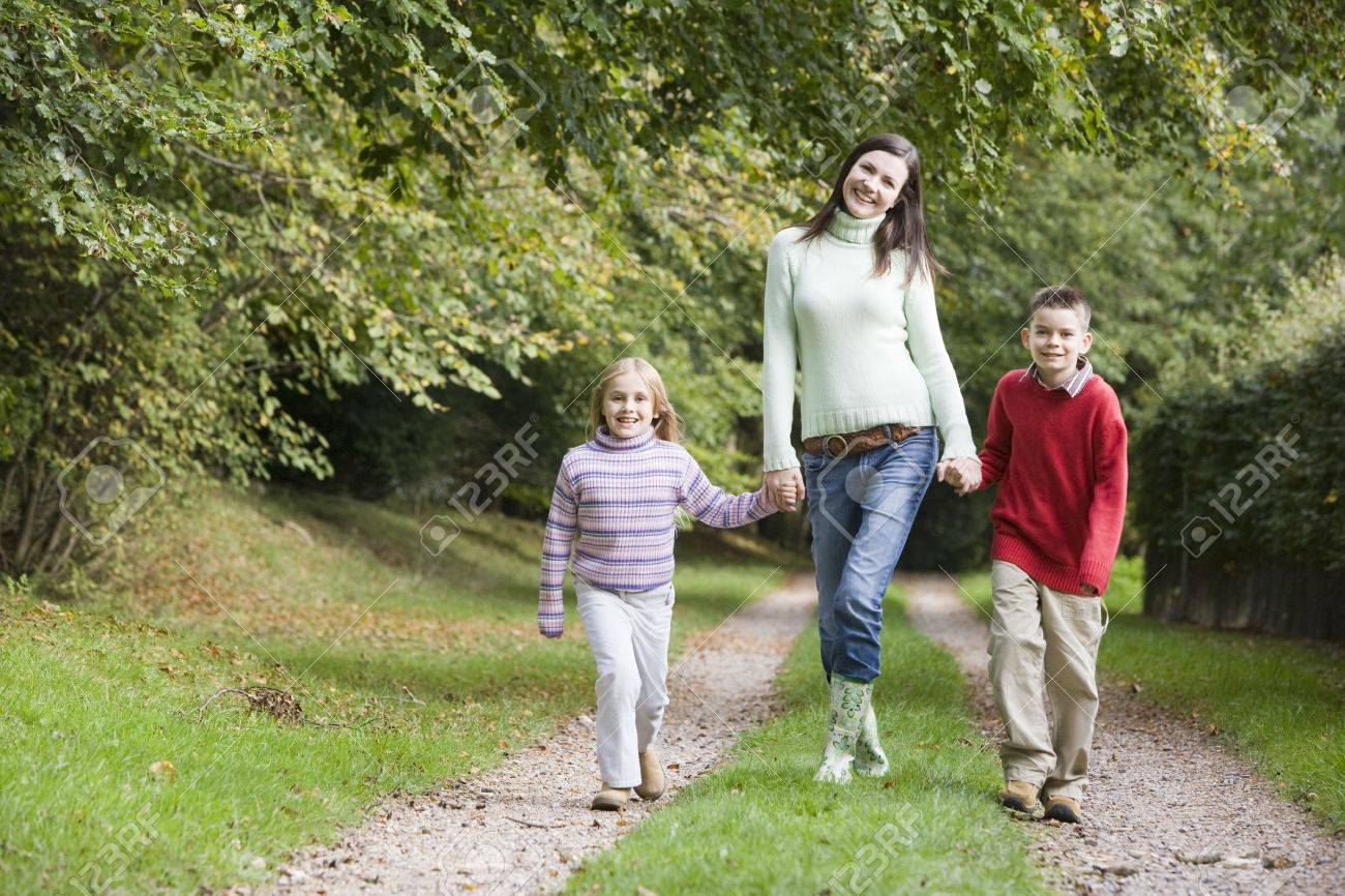 Mother and two children walking on path outdoors smiling (selective focus) Stock Photo - 3207803