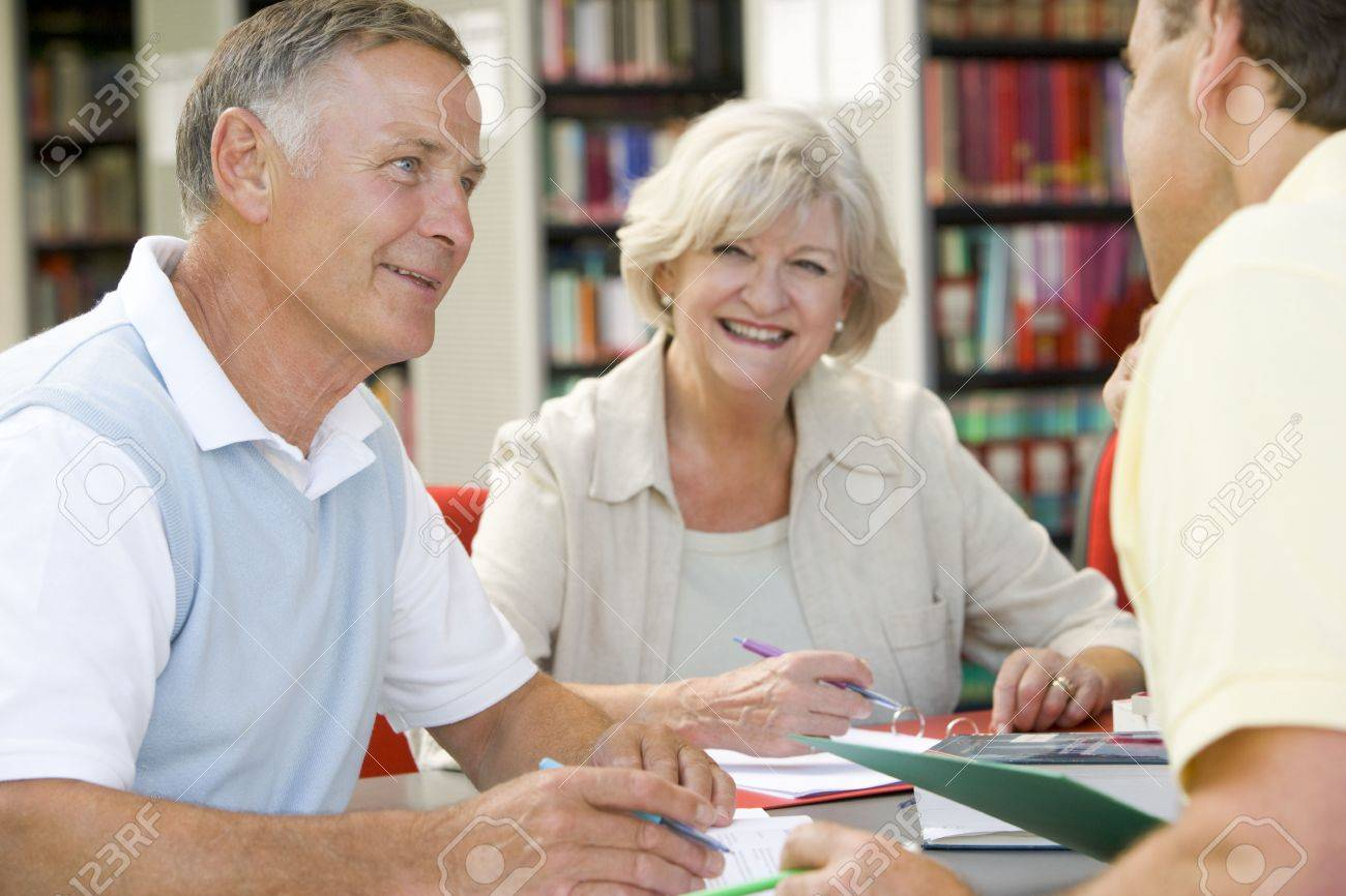 Three people in library writing in notebooks (selective focus) Stock Photo - 4498626