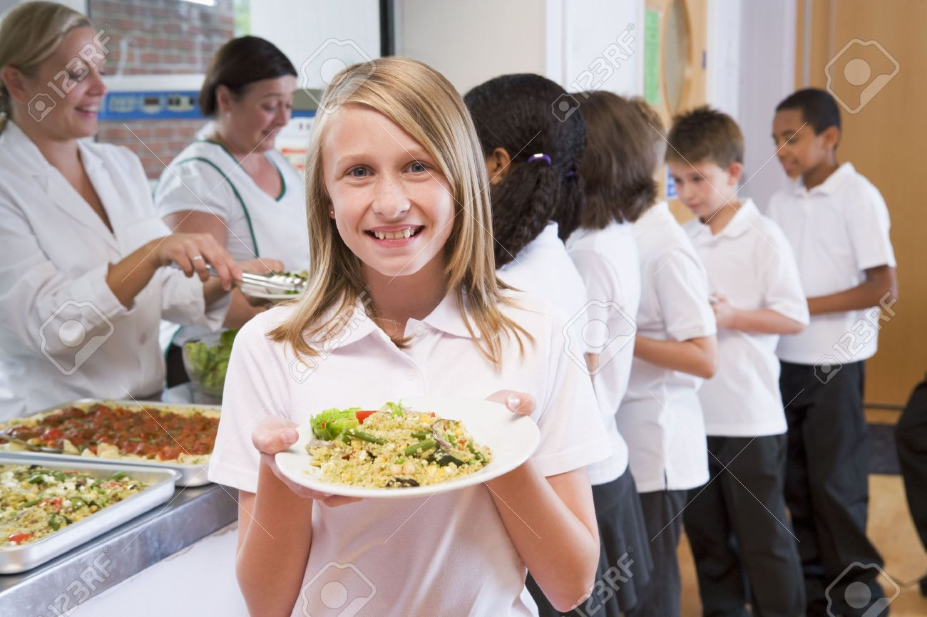 Students in cafeteria line with one holding up her healthy meal and looking at camera (depth of field) Stock Photo - 3223696
