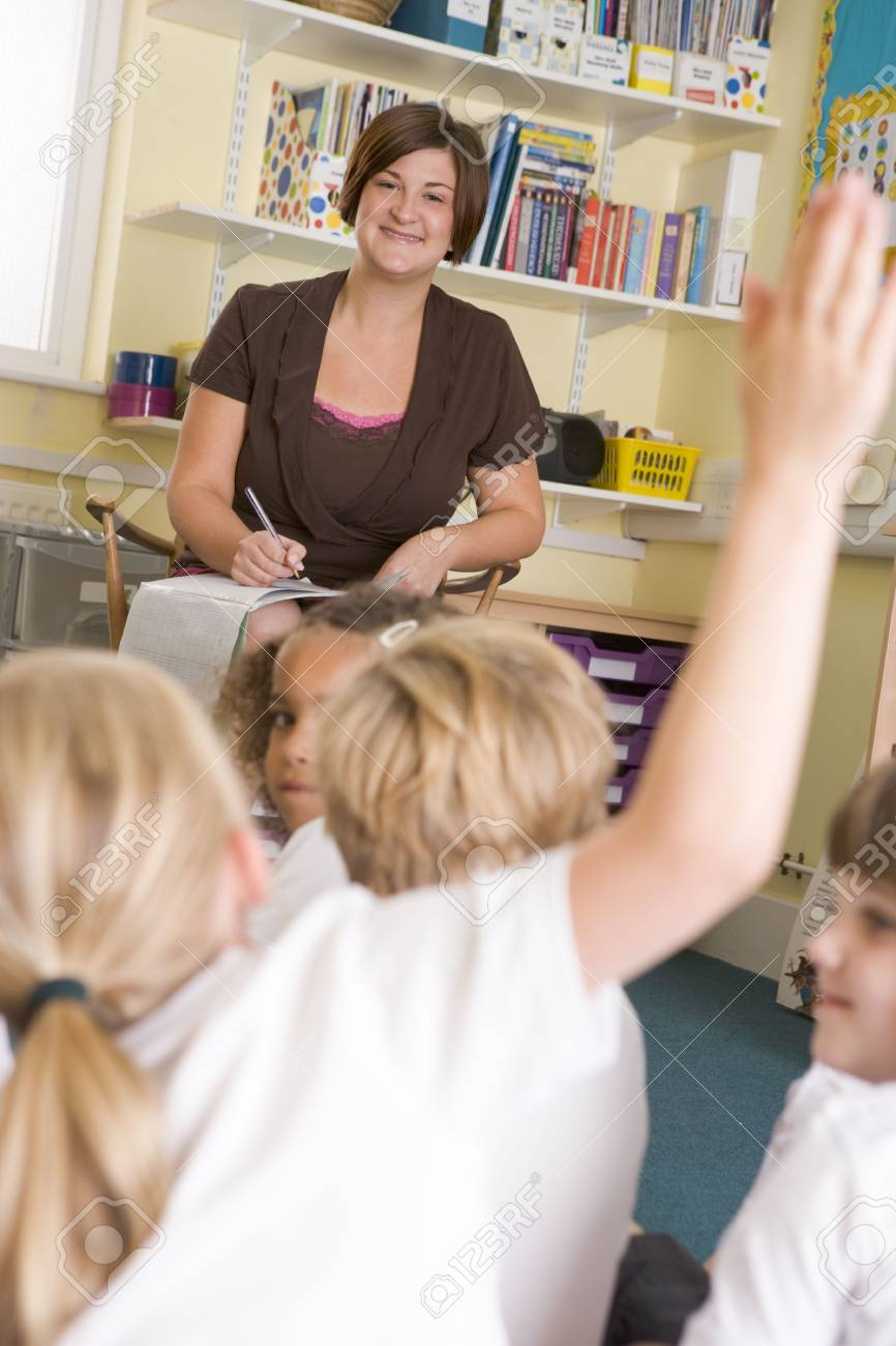 Teacher in class with student volunteering in foreground (selective focus) Stock Photo - 3225261
