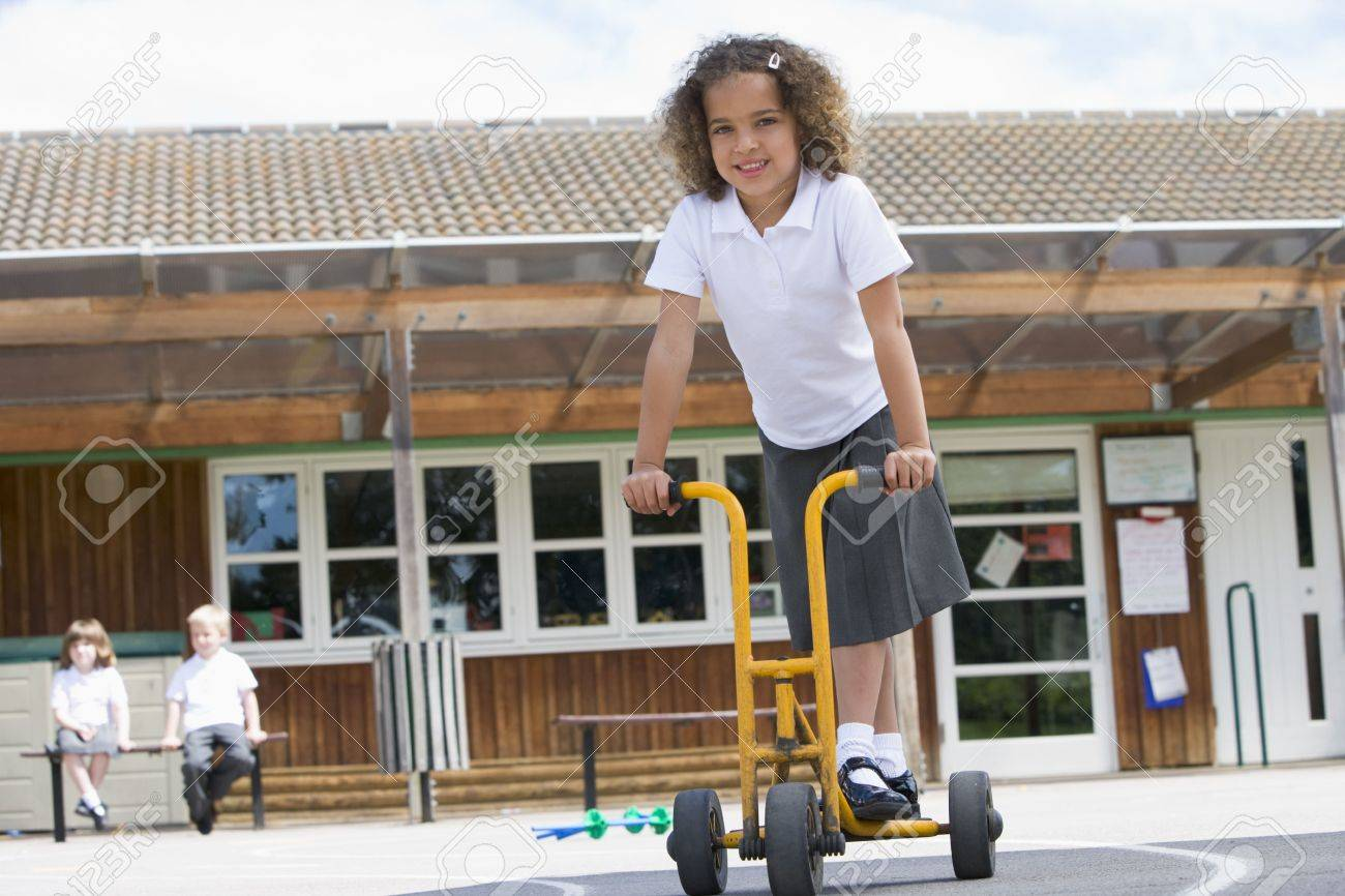 Student outside school on tricycle scooter Stock Photo - 3225414