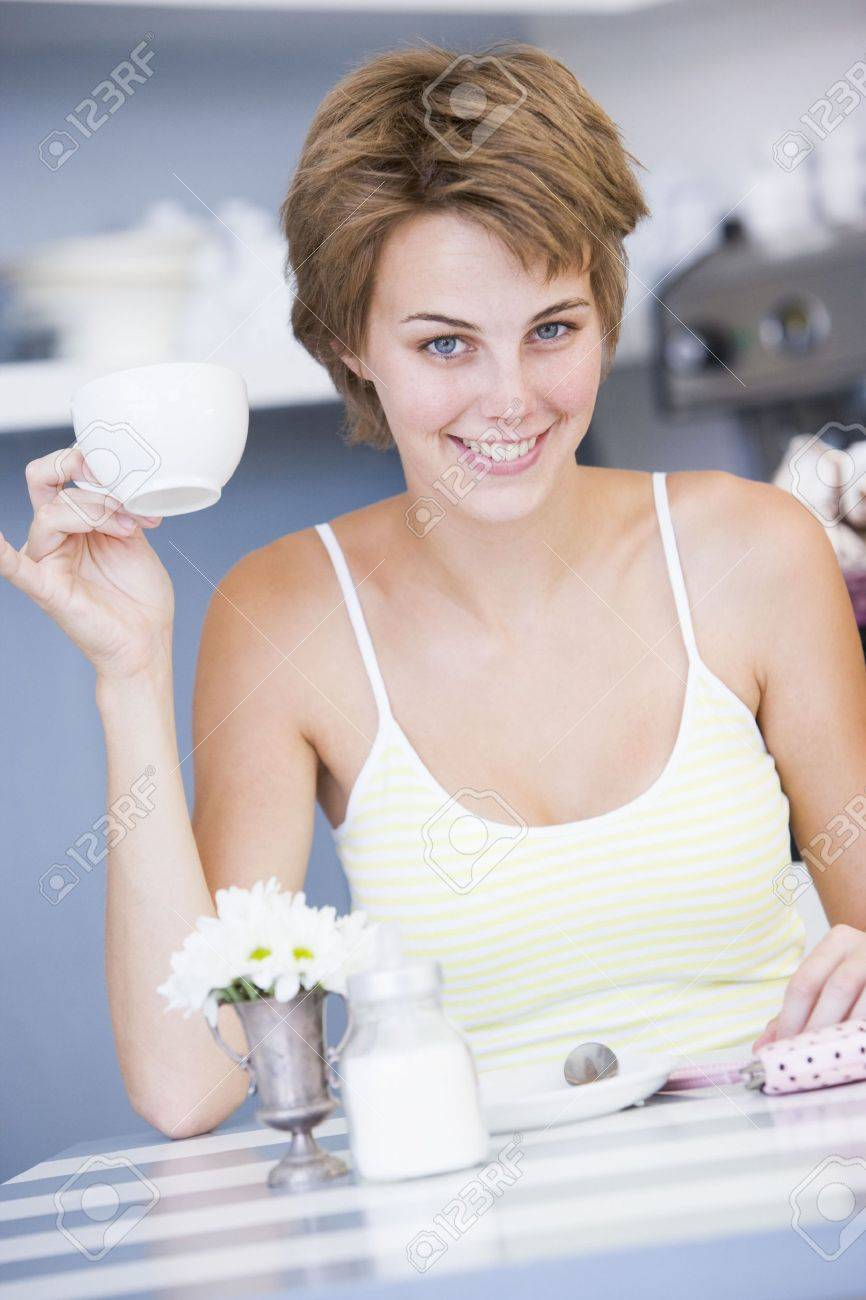 Young woman sitting at a table drinking tea Stock Photo - 3202041