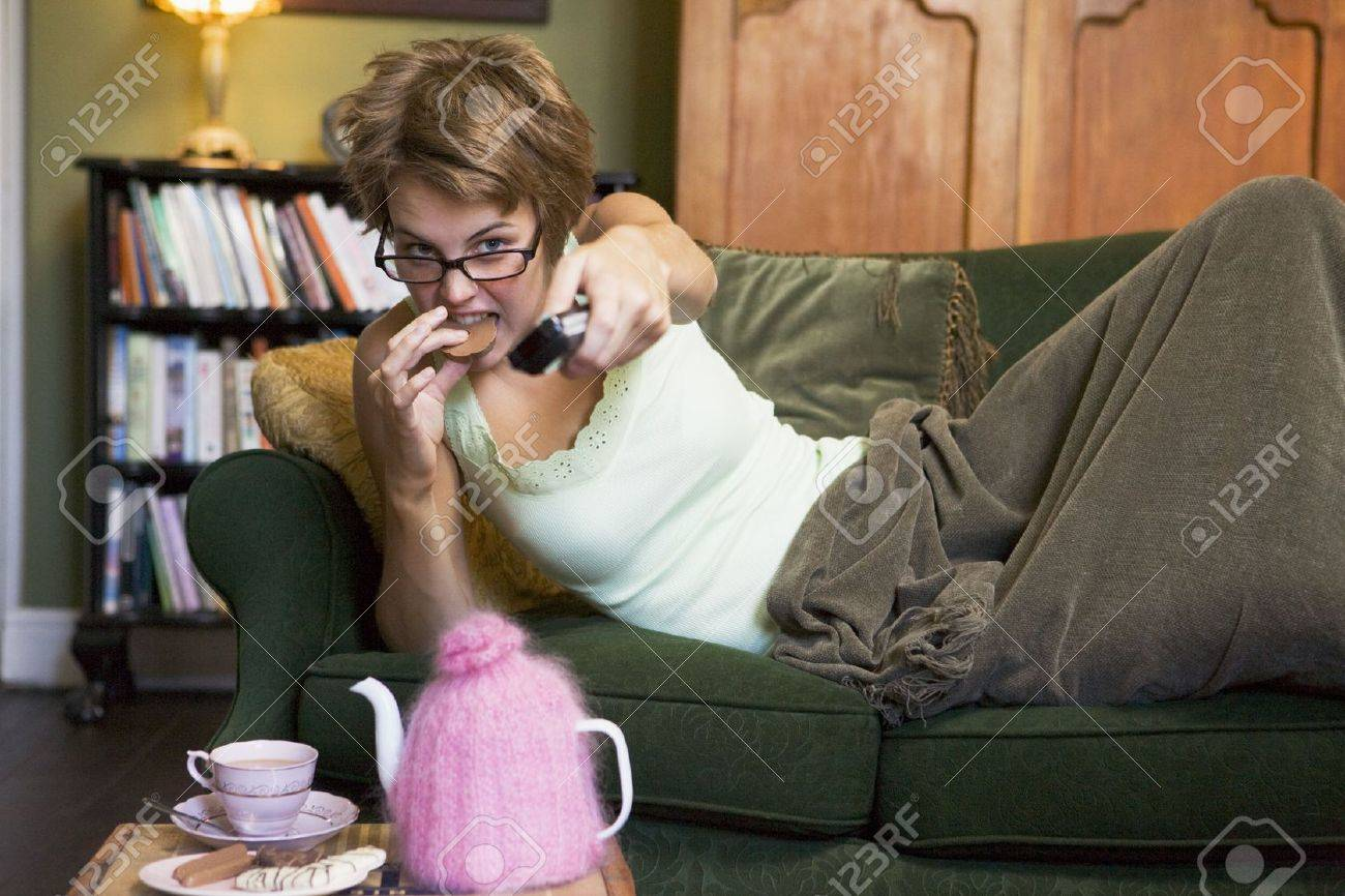 Young woman lying on sofa at home eating cookies and watching television Stock Photo - 3199216