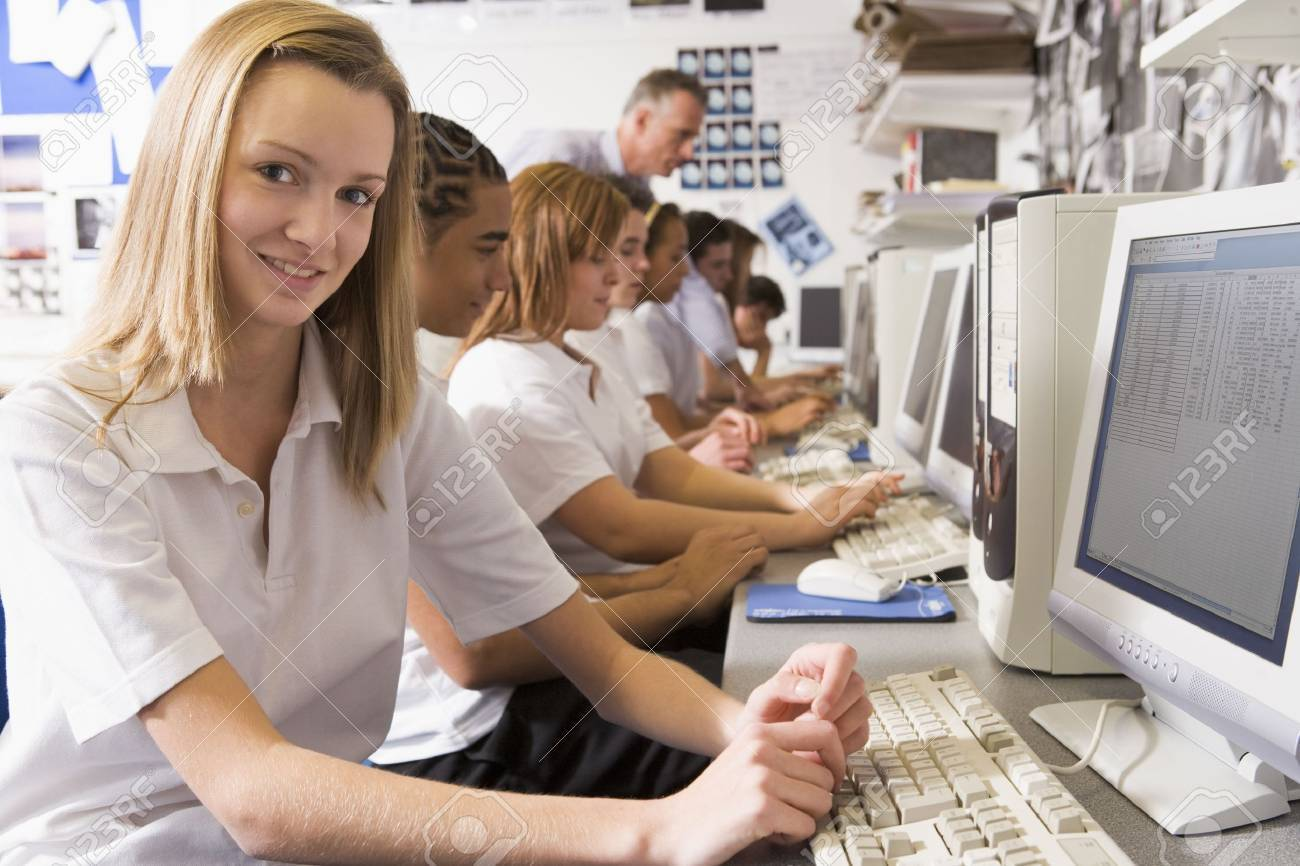 Students working on computer workstations with teacher Stock Photo - 3204282