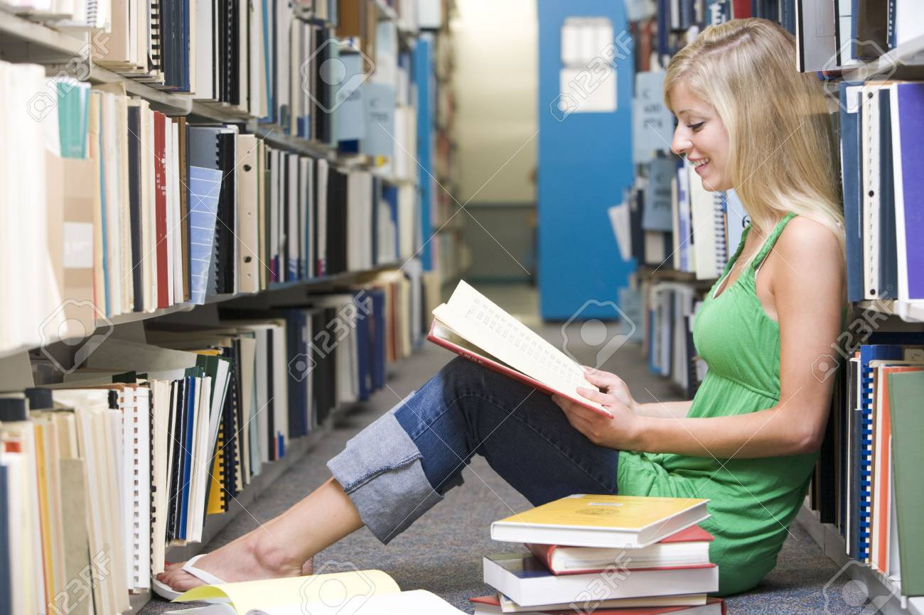 Woman sitting on floor in library reading book Stock Photo - 3201257
