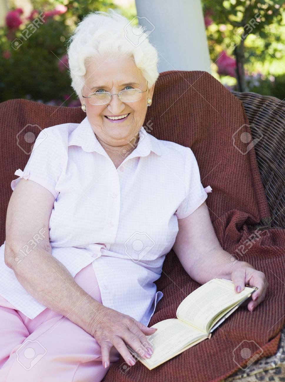 Senior woman sitting outdoors on a chair reading a book Stock Photo - 3177575