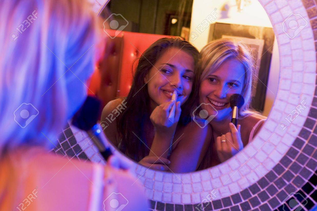 Two young women applying makeup in a mirror Stock Photo - 3205106