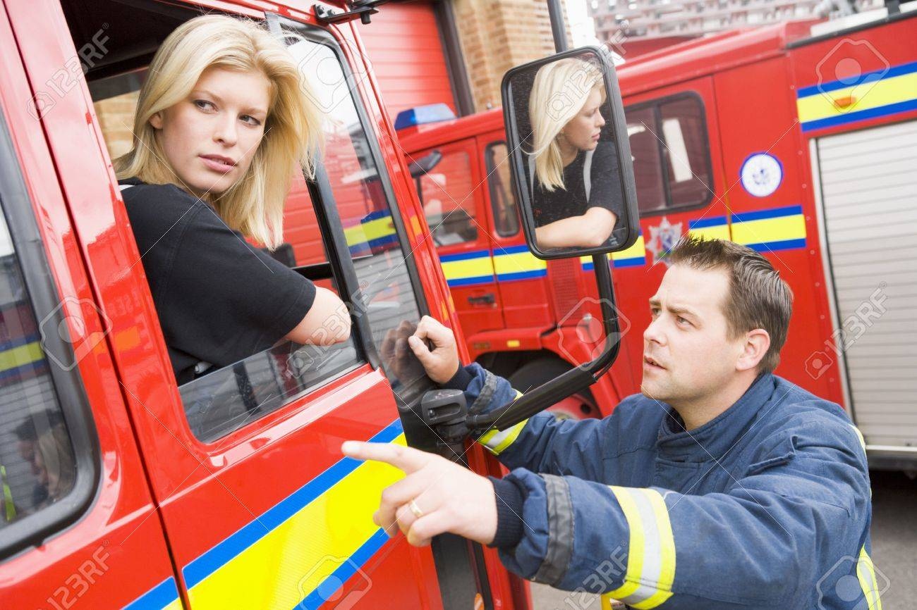 Fireman pointing something out to firewoman sitting in fire engine Stock Photo - 3201466