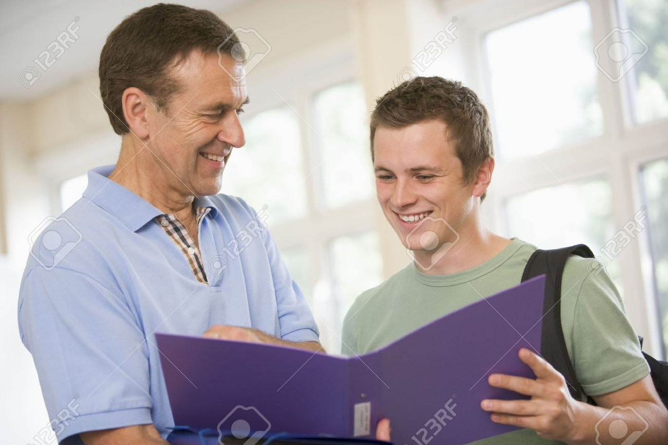Teacher in corridor talking to student with notebooks Stock Photo - 3186184