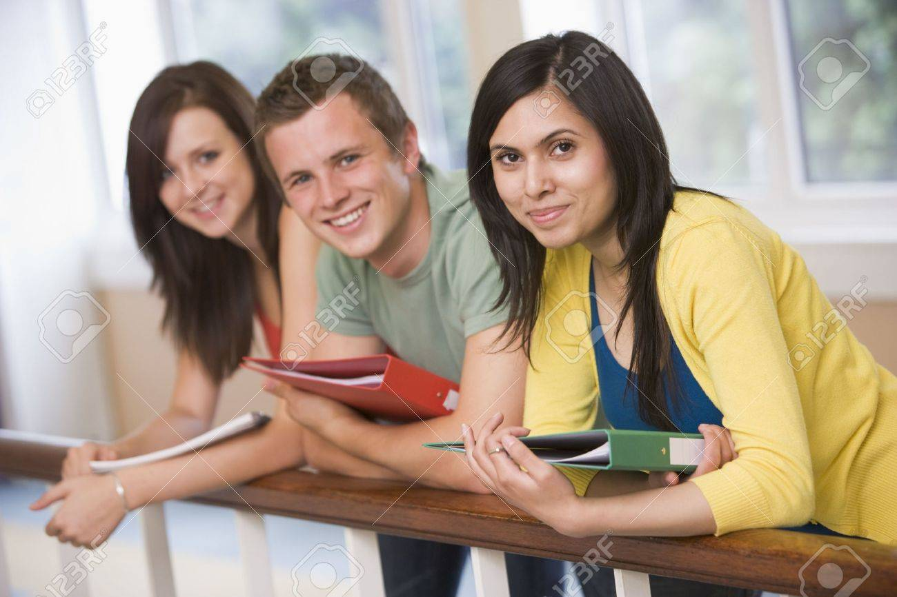 Three students in corridor leaning on railing (depth of field) Stock Photo - 3199449