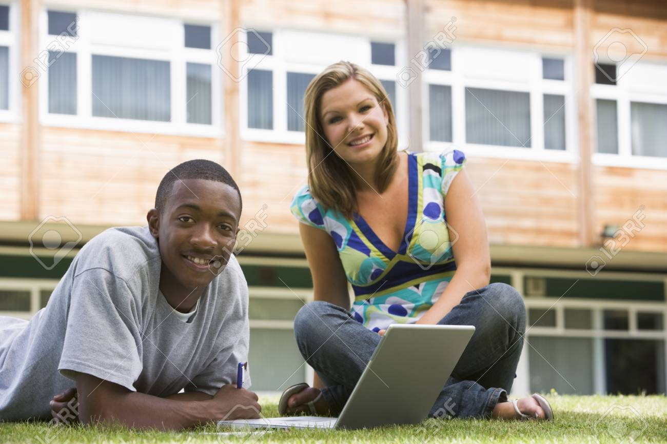 Two students outdoors on lawn with laptop Stock Photo - 3204876