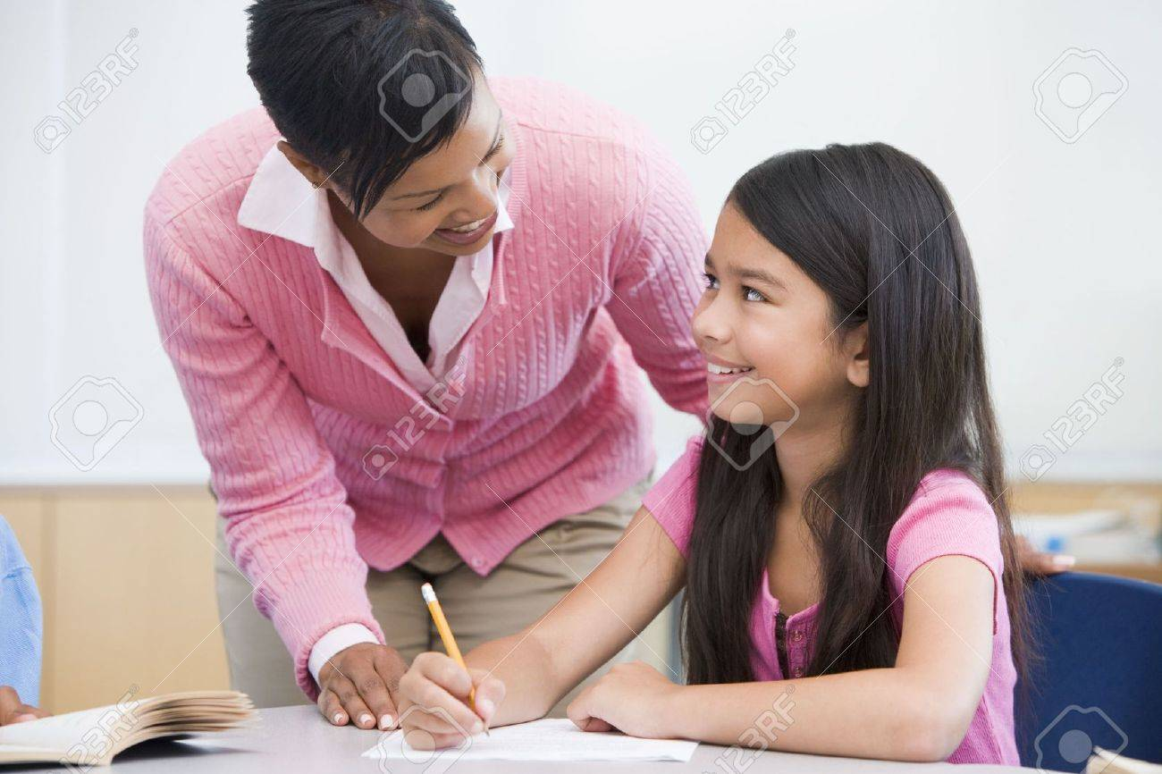 Student in class writing with teacher Stock Photo - 3199533